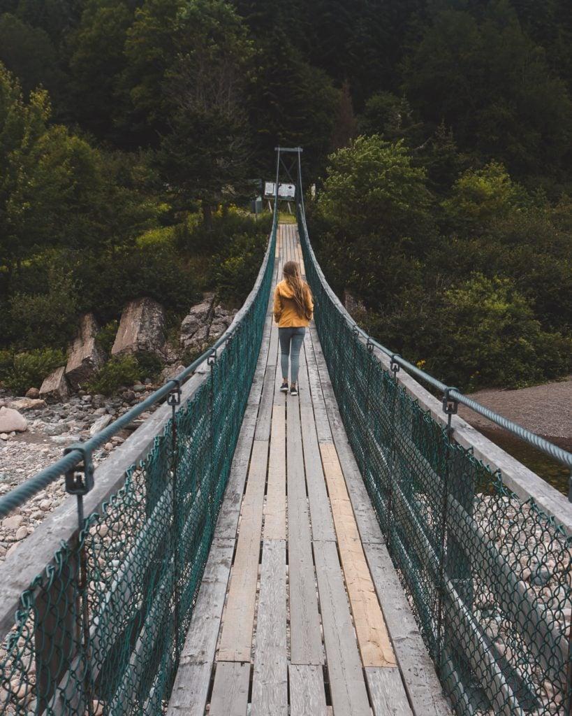 girl walking across suspension bridge