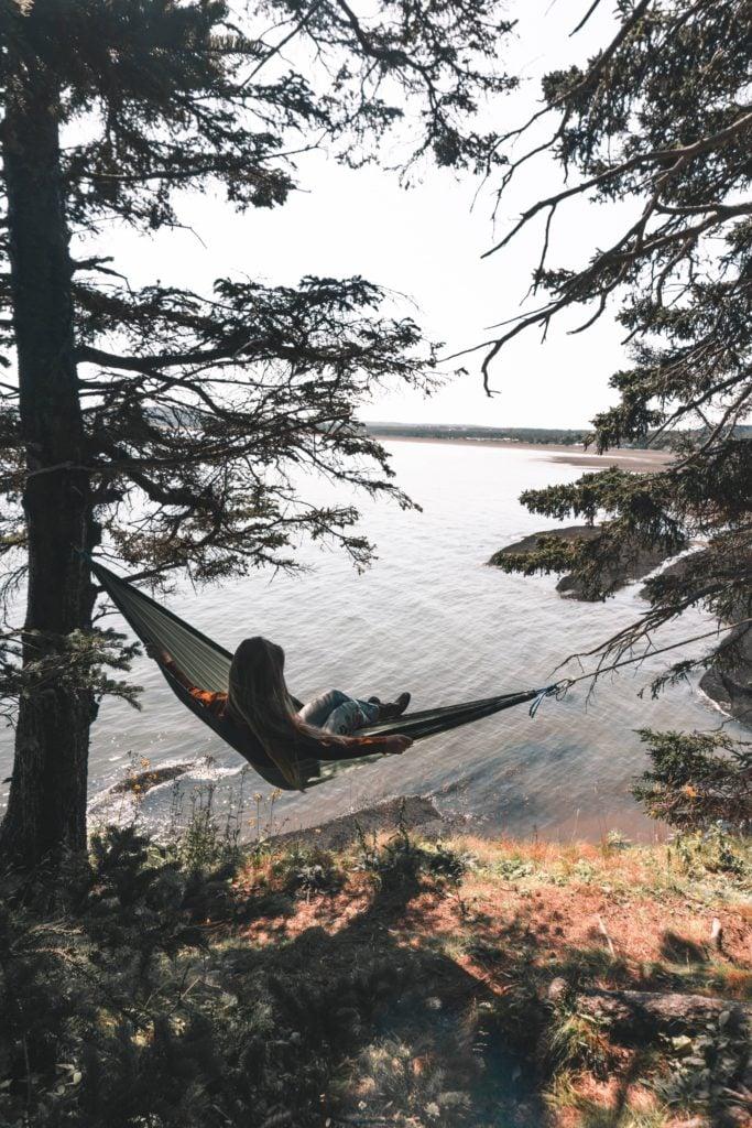 girl swinging in hammock overlooking bay of fundy