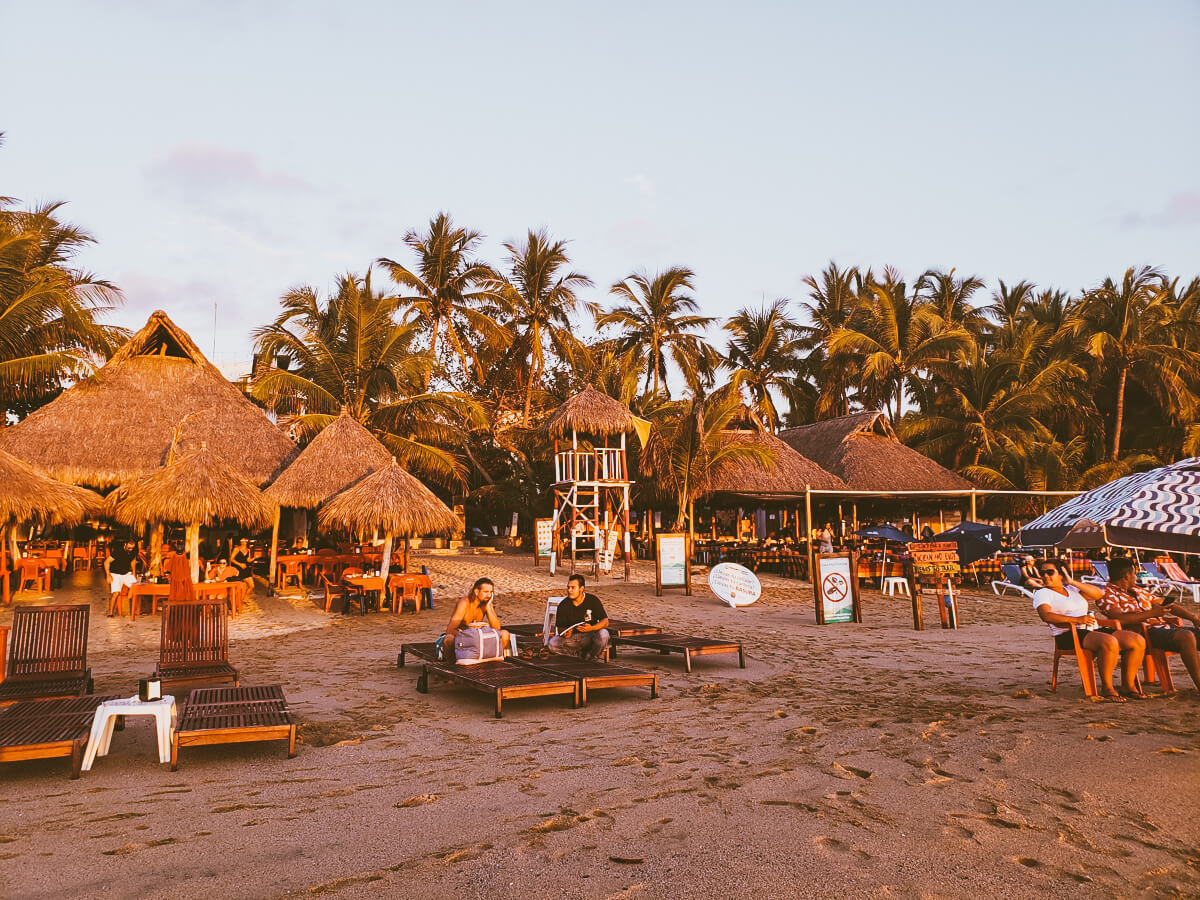 san pancho beach with chairs and palm trees