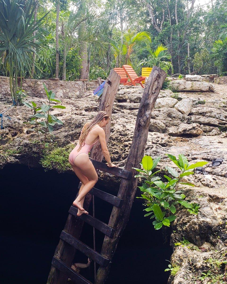 woman climbing ladder in cenote calavera in tulum