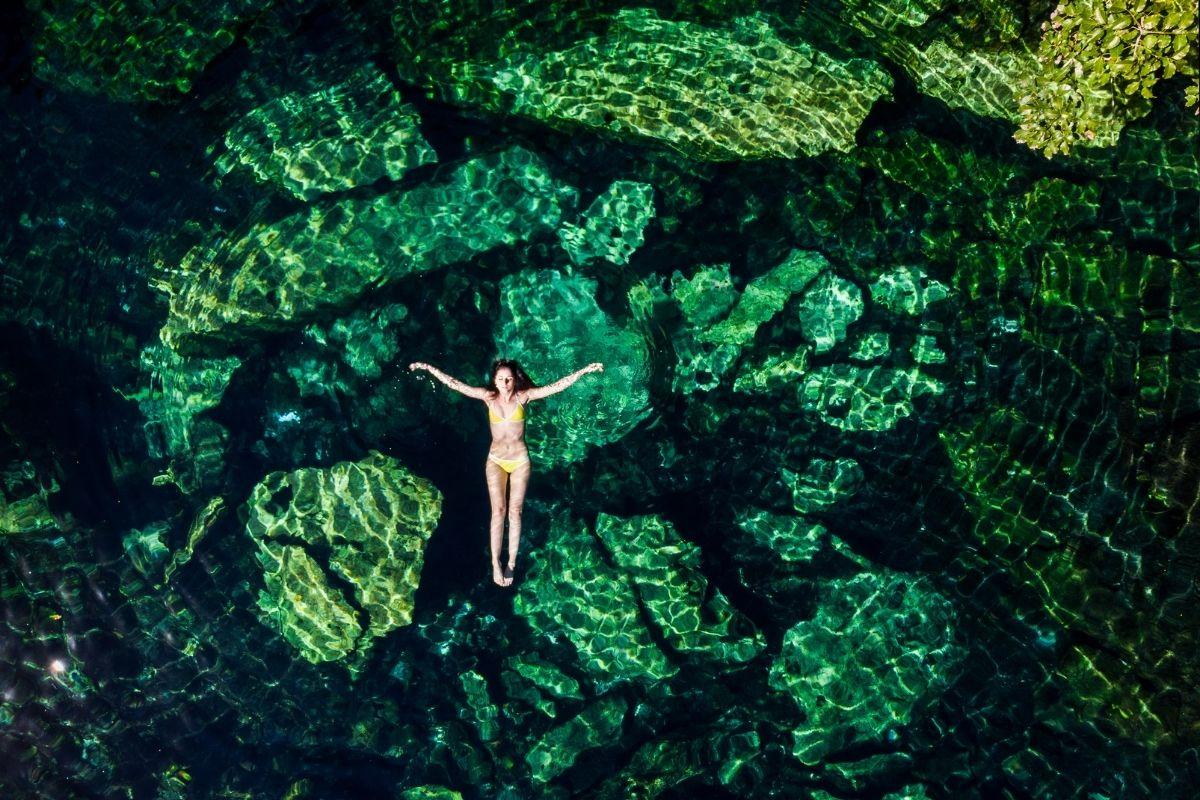woman floating in cenote cristalino near playa del carmen