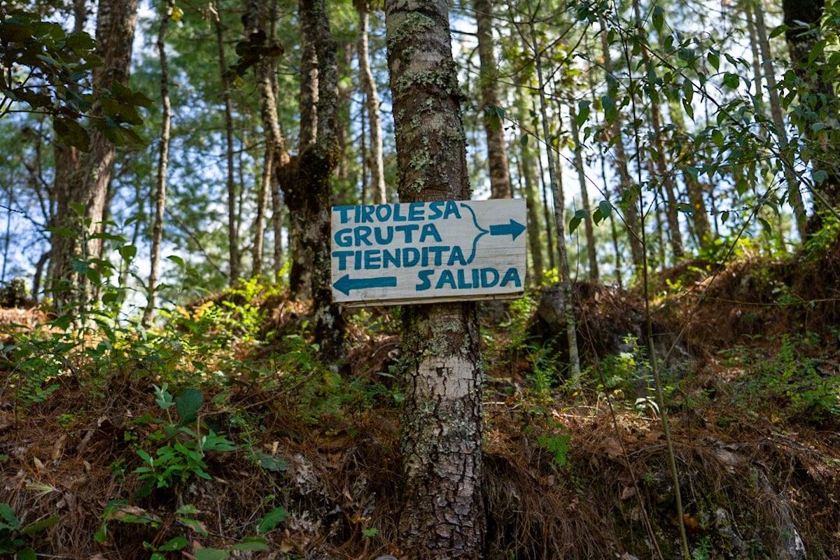 signs pointing to tirolesa gruta and tienda inside arcotete