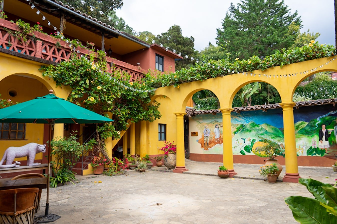 na bolom courtyard and hotel with painted mural and plants