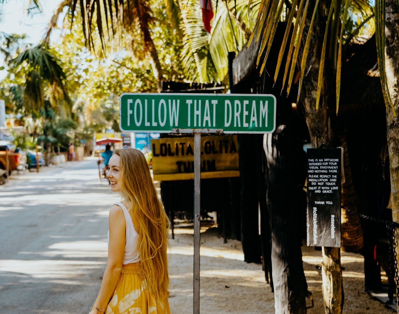 "female digital nomad in front of the ""follow that dream"" sign in tulum, mexico"