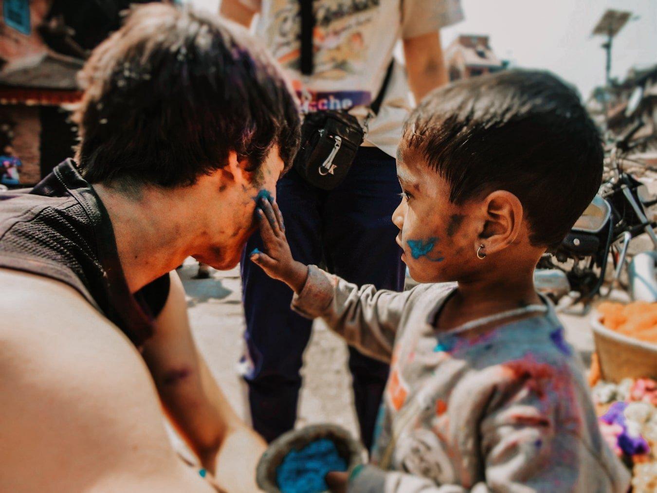 boy putting holi powder on foreigner in kathmandu nepal during the holi festival