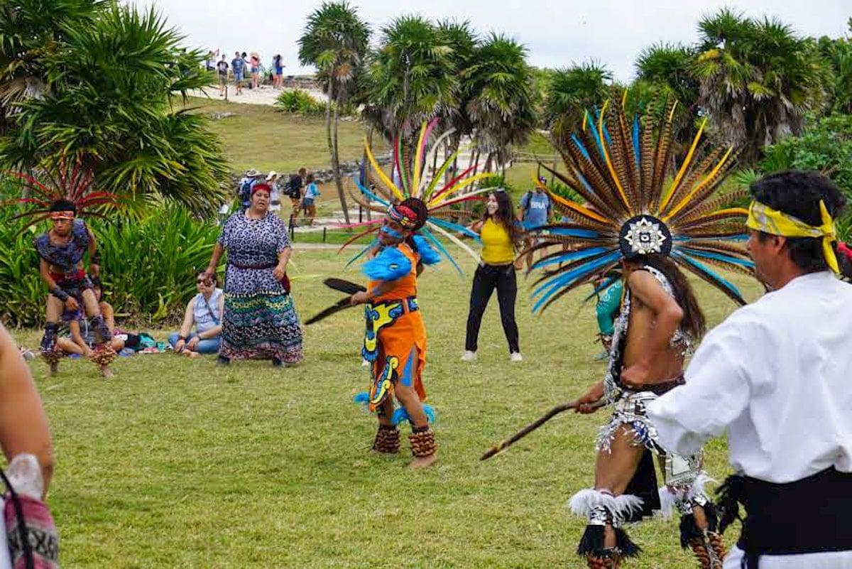 mayan dancers on grass inside tulum ruins park