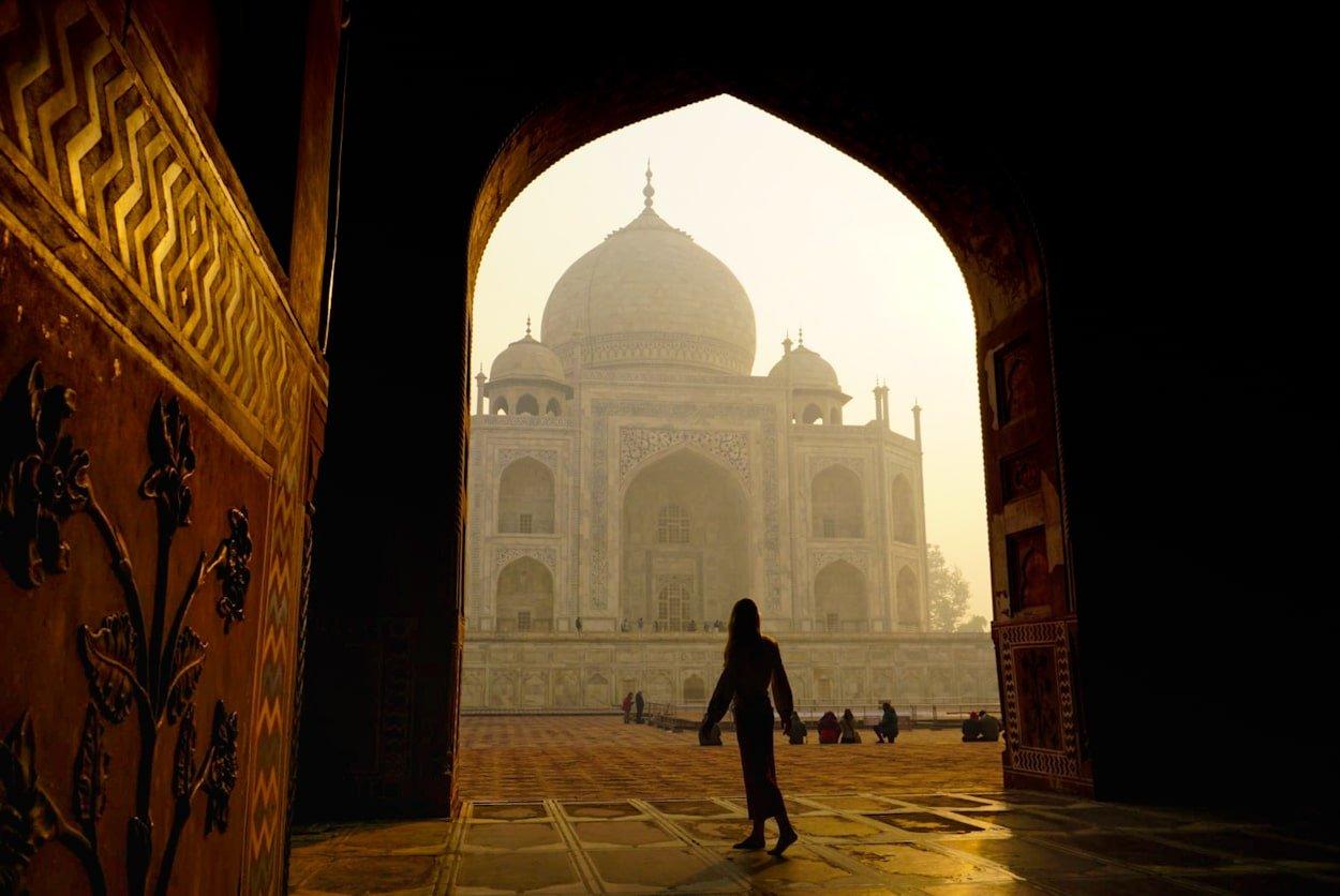 woman in front of taj mahal at sunrise