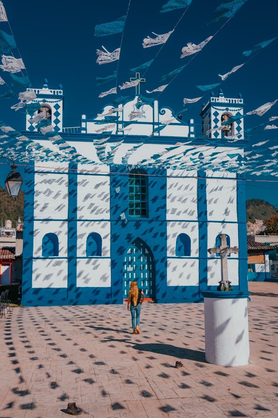 woman at the blue and white templo de san diego in san cristobal de las casas