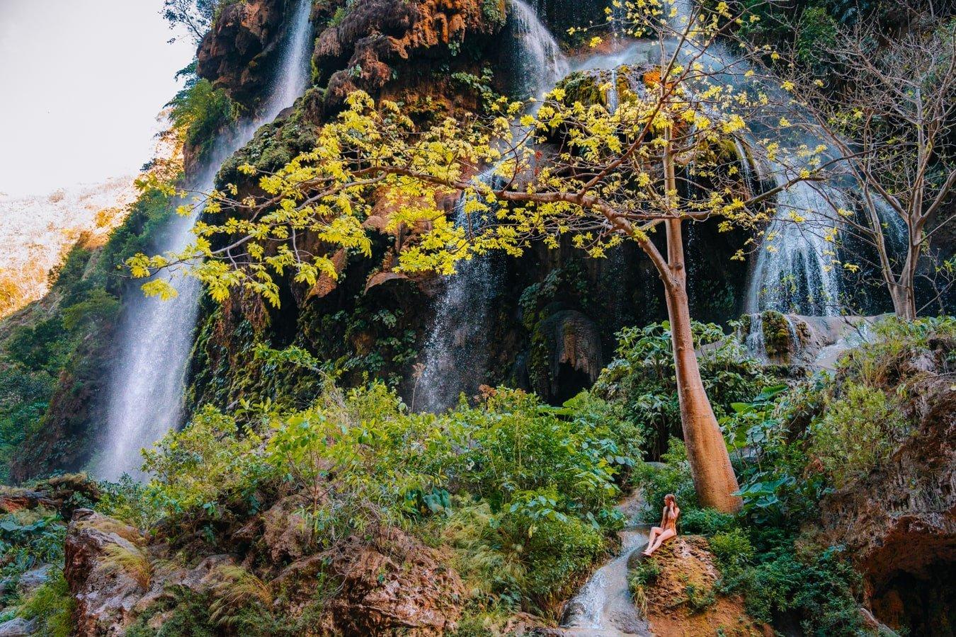 woman sitting on rock at cascada el aguacero chiapas