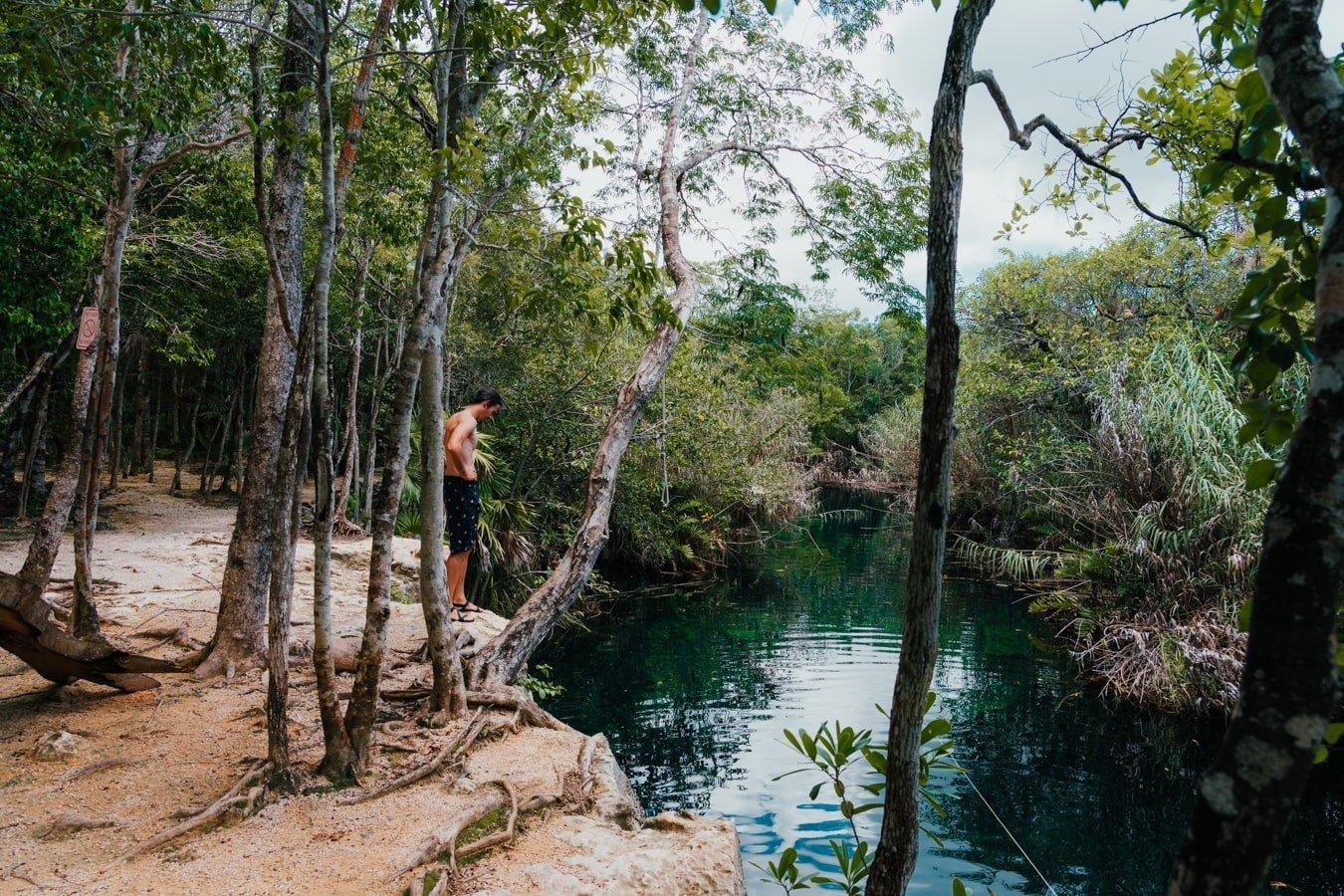 man overlooking cenote escondido in tulum