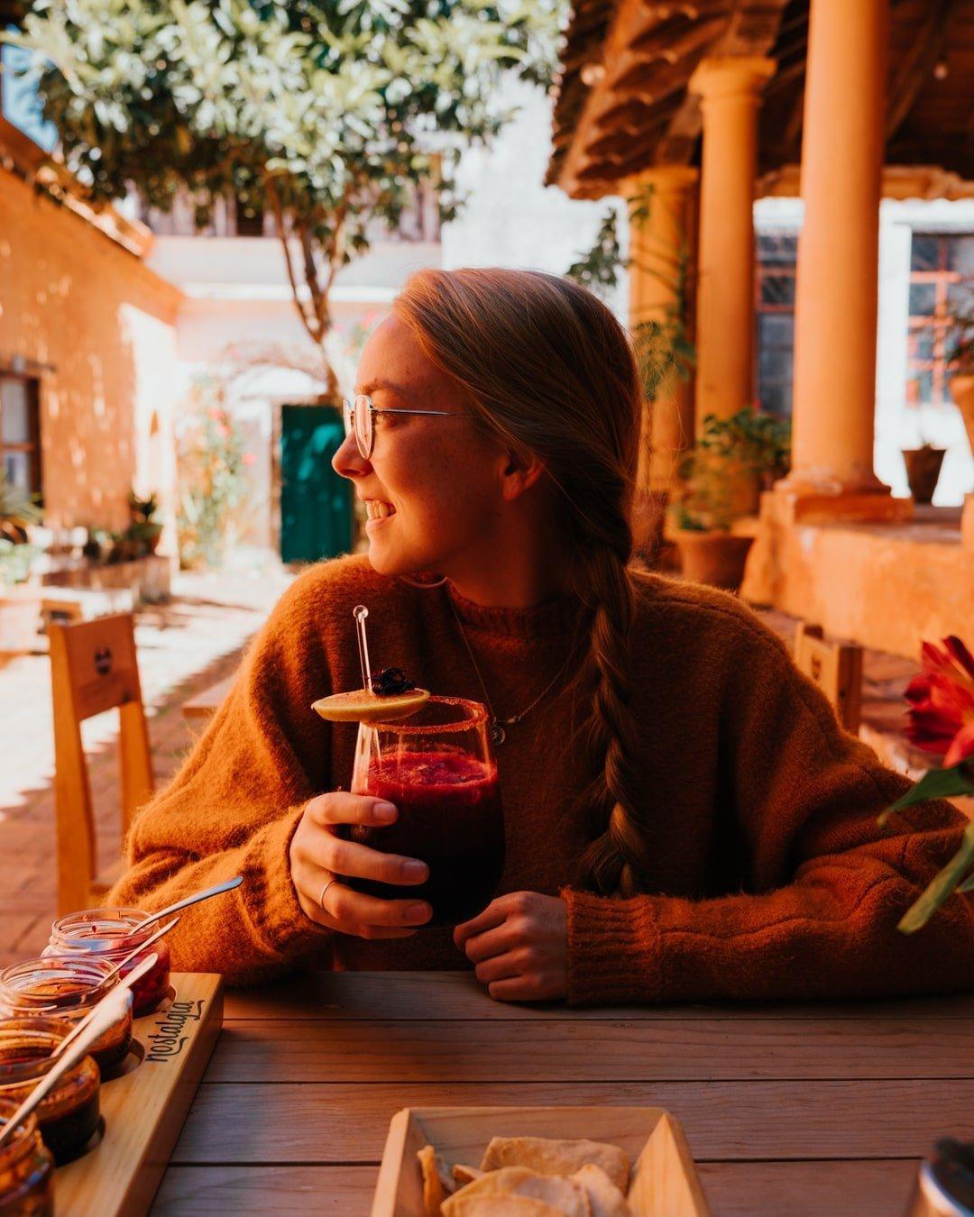 woman holding mezcal cocktail at restaurant san cristobal de las casas